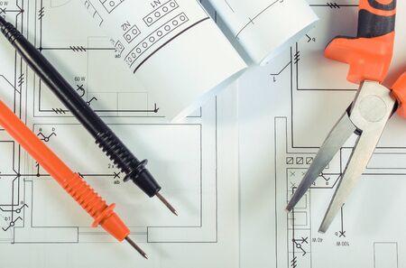 Cavi del multimetro e pinze sui disegni costruttivi della casa. Costruire il concetto di casa. Disegni per lavori di ingegnere di progetti