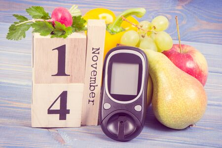 Date 14 November on cube calendar, glucometer for checking sugar level and fresh fruits with vegetables, world diabetes day and fighting disease