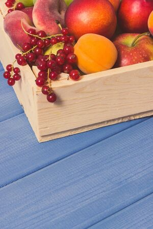 Heap of fresh natural fruits in wooden box. Nutritious food containing healthy minerals and vitamins. Place for text on blue boards