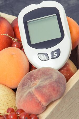 Glucometer for checking sugar level and fresh ripe fruits. Healthy food during diabetes containing natural minerals and vitamins