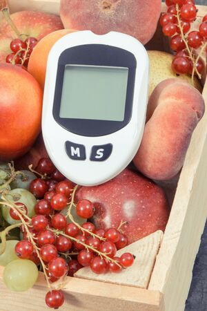 Glucose meter for checking sugar level and healthy fruits containing natural minerals and vitamins. Concept of diabetes, slimming and dieting Imagens
