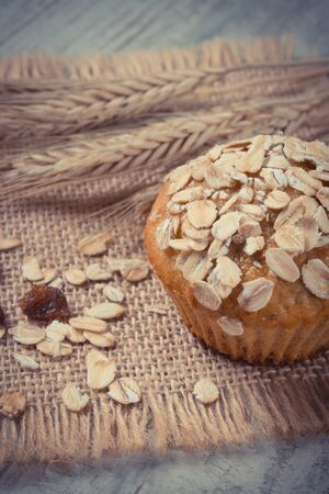 Vintage photo. Fresh muffin with oatmeal baked with wholemeal flour and ears of rye grain, concept of delicious, healthy dessert or snack