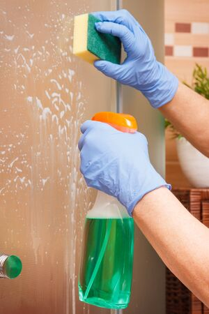 Hand of senior woman in protective gloves using sponge with detergent for cleaning glass shower door, concept of household duties