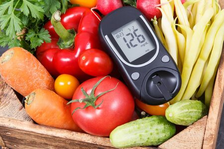 Glucose meter with result of sugar level and fresh ripe vegetables in wooden box as healthy snack containing natural minerals and vitamins