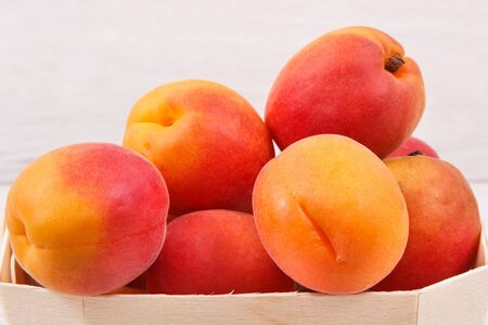 Apricot or peach in wooden box as healthy snack or dessert. Food containing natural vitamins and minerals