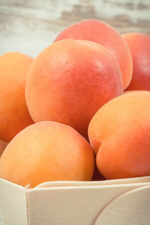 Fresh apricot in wooden box as healthy snack or dessert containing natural vitamins