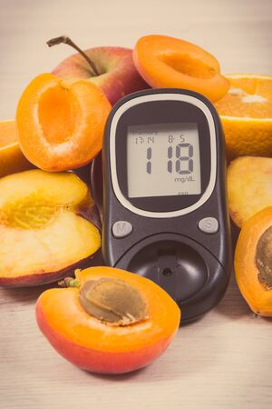 Glucose meter with result sugar level and fruits containing nutritious vitamins and minerals for healthy lifestyles of diabetics. Vintage photo