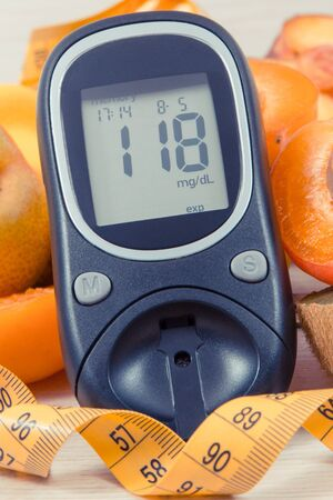 Glucose meter for measuring sugar level, tape measure and fruits containing nutritious vitamins and minerals for healthy lifestyles of diabetics Stok Fotoğraf - 132094371