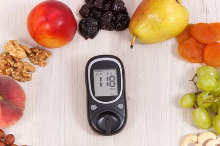 Glucose meter for measuring sugar level and fresh ripe nutritious food as source vitamins, dietary fiber and natural minerals Standard-Bild - 133199910