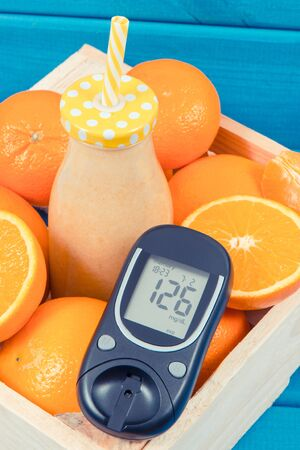 Glucometer with result of sugar level and cocktail or smoothie from citrus fruits.