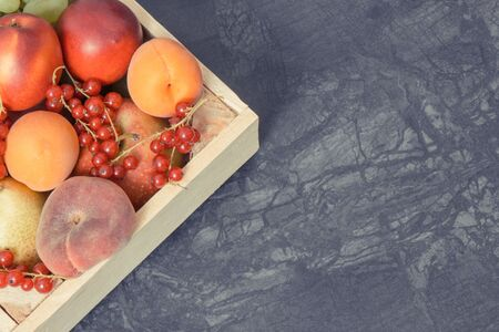 Fresh natural fruits in wooden box. Nutritious food containing healthy minerals and vitamins. Place for text or inscription