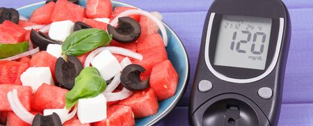 Glucometer for checking sugar level and summer salad of watermelon with feta cheese.