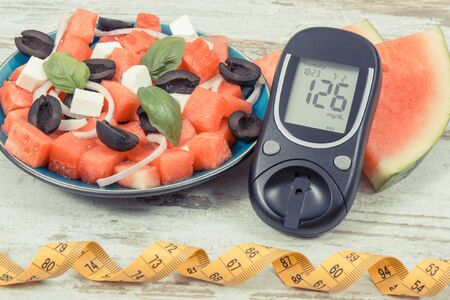 Glucometer for checking sugar level and fresh summer salad of watermelon with feta cheese Zdjęcie Seryjne
