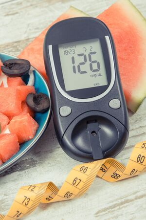 Glucometer for checking sugar level and fresh summer salad of watermelon with feta cheese. Zdjęcie Seryjne