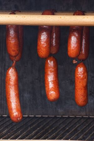 Smoked homemade sausages meat hanging in smokehouse