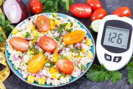 Glucometer with result of sugar level, salad with vegetables and bulgur groats, tape measure. Diabetes and healthy meal containing natural vitamins and minerals