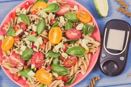Glucometer and fresh prepared salad with wholegrain pasta and vegetables. Diabetes, dieting and healthy nutrition Zdjęcie Seryjne