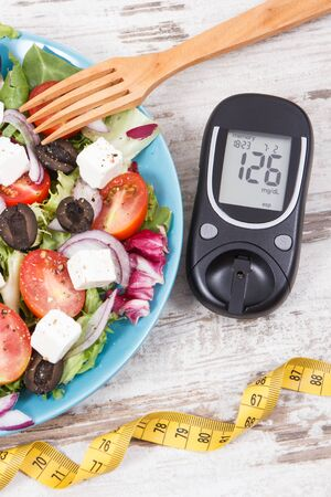 Glucometer for checking sugar level, tape measure and fresh prepared greek salad. Diabetes and healthy lifestyles concept