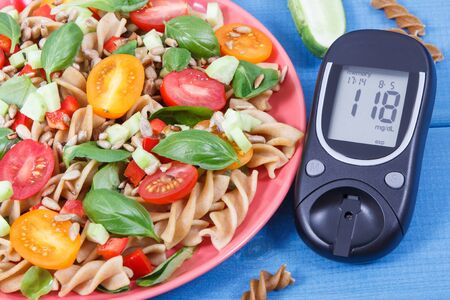 Glucose meter for checking sugar level and fresh prepared salad with wholegrain pasta and vegetables. Best food for diabetics Zdjęcie Seryjne