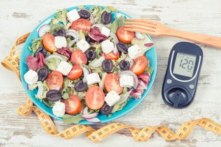 Glucose meter and fresh prepared greek salad with feta cheese and vegetables. Best healthy food for diabetics, dieting and slimming