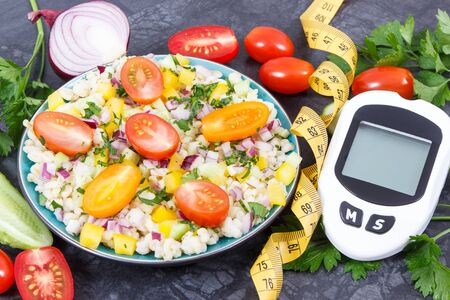 Glucose meter for analyzing sugar level and fresh salad with bulgur groats and vegetables. Diabetes, slimming and healthy lifestyles and nutrition concept