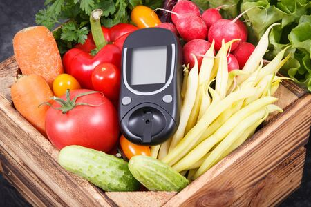 Glucose meter for measuring sugar level and fresh ripe vegetables in wooden box as healthy snack containing natural minerals and vitamins