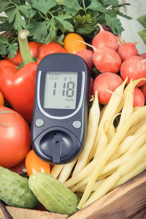 Glucometer with fresh ripe vegetables as source natural minerals and vitamins. Diabetes, healthy lifestyles and dieting concept Zdjęcie Seryjne