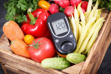 Glucometer for checking sugar level and fresh ripe vegetables as healthy ingredients containing vitamins and minerals using during diabetes