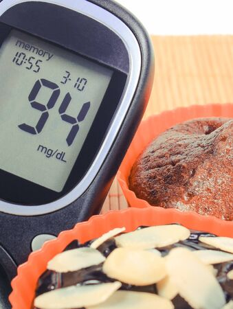 Glucose meter with result of sugar level and fresh baked homemade chocolate muffins. Delicious dessert for diabetics Zdjęcie Seryjne