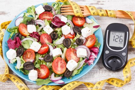 Glucometer with result of sugar level, cintimeter and fresh greek salad with feta cheese and vegetables. Best healthy food for diabetics, dieting and slimming Zdjęcie Seryjne