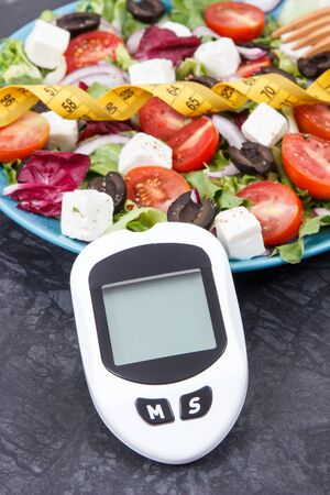 Glucose meter for checking sugar level, tape measure and fresh greek salad. Best food for diabetics and slimming containing natural vitamins Zdjęcie Seryjne