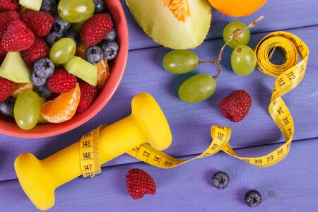 Fresh fruit salad, tape measure and dumbbells for using in fitness, concept of sport, diet, slimming, healthy lifestyles and nutrition Stock fotó