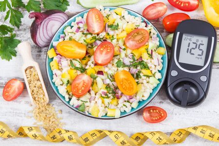 Glucose meter for checking sugar level and fresh salad with bulgur groats and vegetables as best food containing vitamins and minerals for diabetics, dieting and slimming