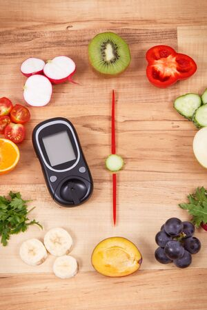 Glucometer with clock made of ripe fruits and vegetables, concept of healthy dinner for diabetics Zdjęcie Seryjne