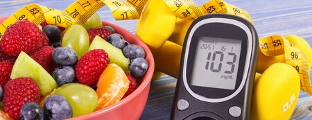Fresh fruit salad, glucose meter with result of sugar level, tape measure and dumbbells for fitness, concept of diabetes, sport, diet, slimming, healthy lifestyles and nutrition