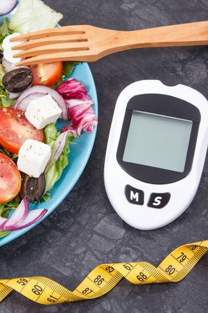 Glucometer, tape measure and fresh prepared greek salad with feta cheese and vegetables. Checking sugar level and slimming concept