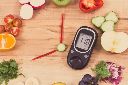 Glucose meter with result of sugar level and clock made of ripe fruits with vegetables containing vitamins and showing time for breakfast