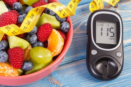 Fresh fruit salad, glucose meter with result of measurement sugar level and tape measure, concept of diabetes, diet, slimming, healthy lifestyles and nutrition