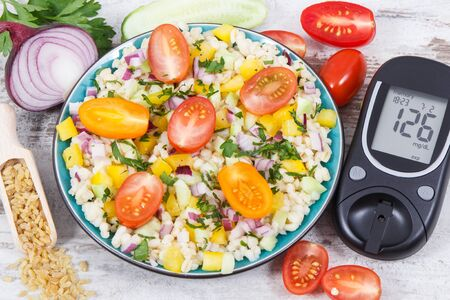 Glucose meter with result of sugar level, salad with vegetables and bulgur groats, tape measure. Diabetes and healthy meal containing natural vitamins and minerals