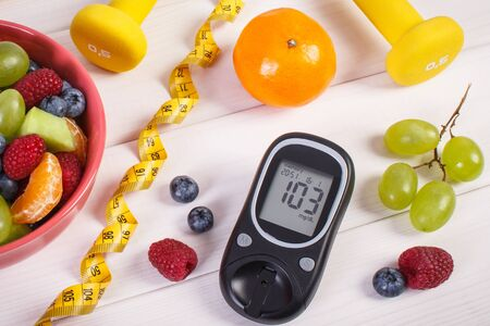 Fresh fruit salad, glucometer with result of sugar level, tape measure and dumbbells for fitness, concept of diabetes, sport, diet, slimming, healthy lifestyles and nutrition Stock fotó