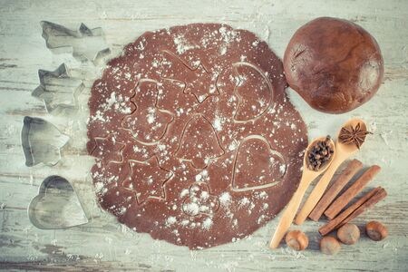 Vintage photo, Dough for Christmas cookies with spice and ingredients for baking gingerbread on old rustic board