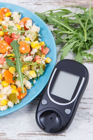 Glucose meter for checking sugar level and fresh salad with vegetables and couscous groats. Light and healthy meal for diabetics containing vitamins and minerals