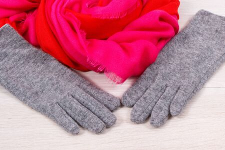 Pair of gray warm womanly woolen gloves and colorful shawl for using in autumn or winter
