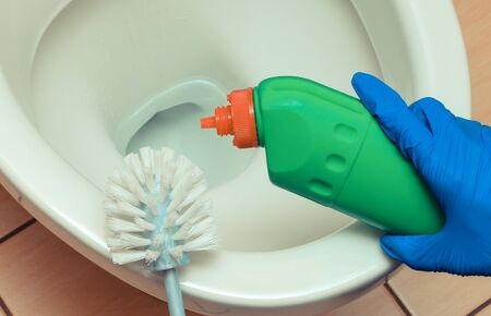 Hand in blue glove cleaning toilet bowl using brush and chemical detegent. House cleaning and household duties concept