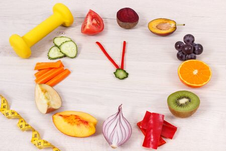 Clock made of fruits and vegetables showing time of 23 hours 55 minutes, dumbbell and centimeter, time for new year resolutions concept