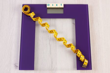 Tape measure on digital bathroom scale for weight of human body, concept of healthy lifestyle and slimming