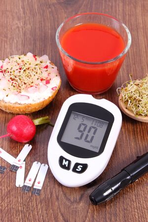 Glucose meter with accessories for checking and measuring sugar level, freshly vegetarian sandwich with cottage cheese and vegetables