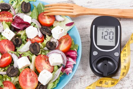 Glucometer with result of sugar level, cintimeter and fresh greek salad with feta cheese and vegetables. Best healthy food for diabetics, dieting and slimming 写真素材