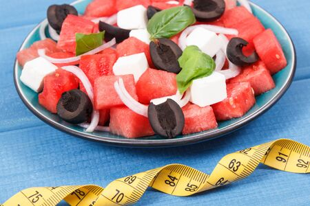 Fresh summer salad of watermelon with feta cheese and tape measure. Slimming, healthy lifestyles and nutrition concept 写真素材