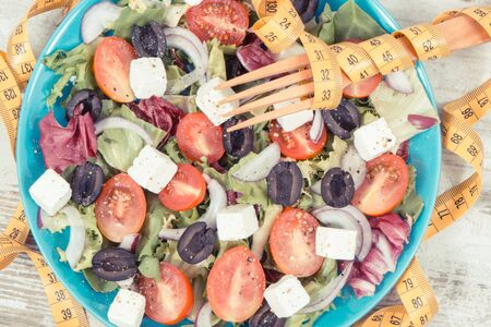 Tape measure with fresh prepared healthy greek salad with feta cheese and vegetables. Best food for dieting and slimming concept